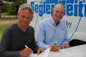 Ilja Wolf (BYC, li.) und Klaus Lahme (NRV, re.) unterzeichnen den Kooperationsvertrag; Foto: Segler-Zeitung